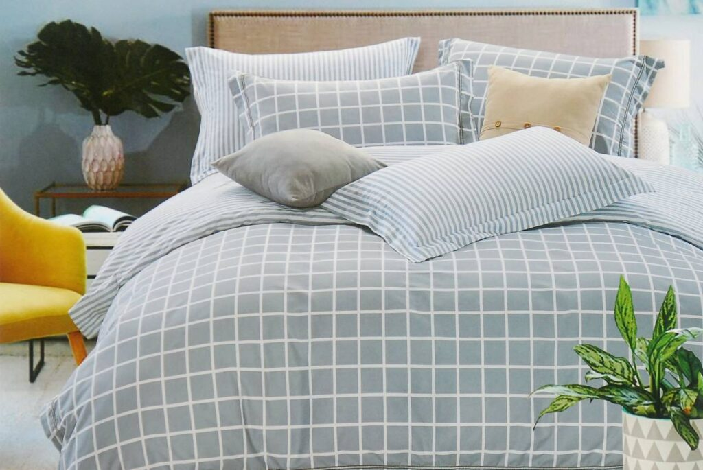 Bright and clean bed with blue bedding for bed linen care tips.