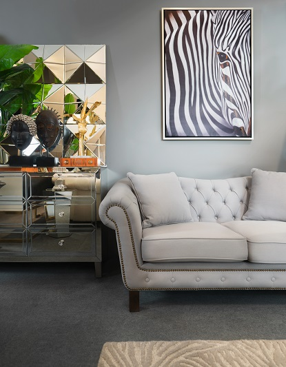 Another decor look still in vogue: Living room set up with pale grey sofa, pyramid-textured mirror and zebra painting.