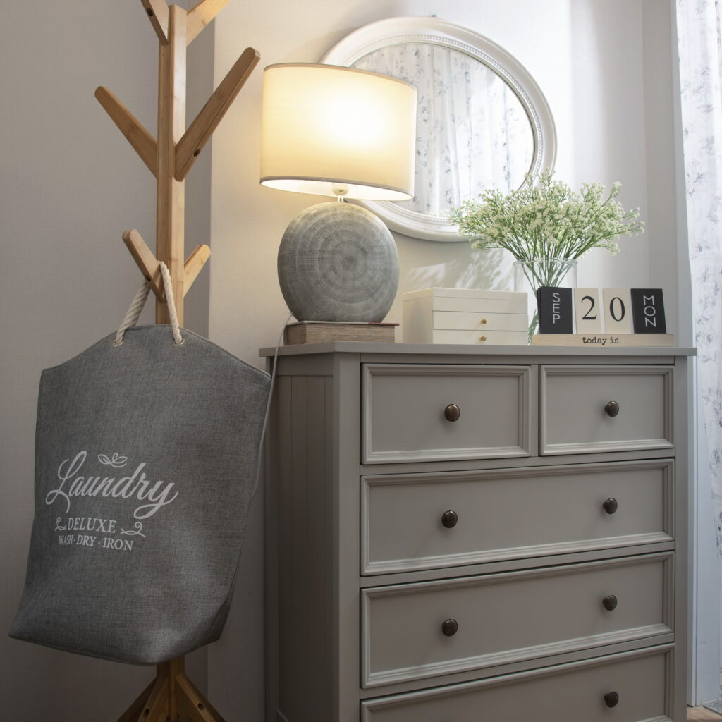 Chest of drawers in bedroom with laundry bag.