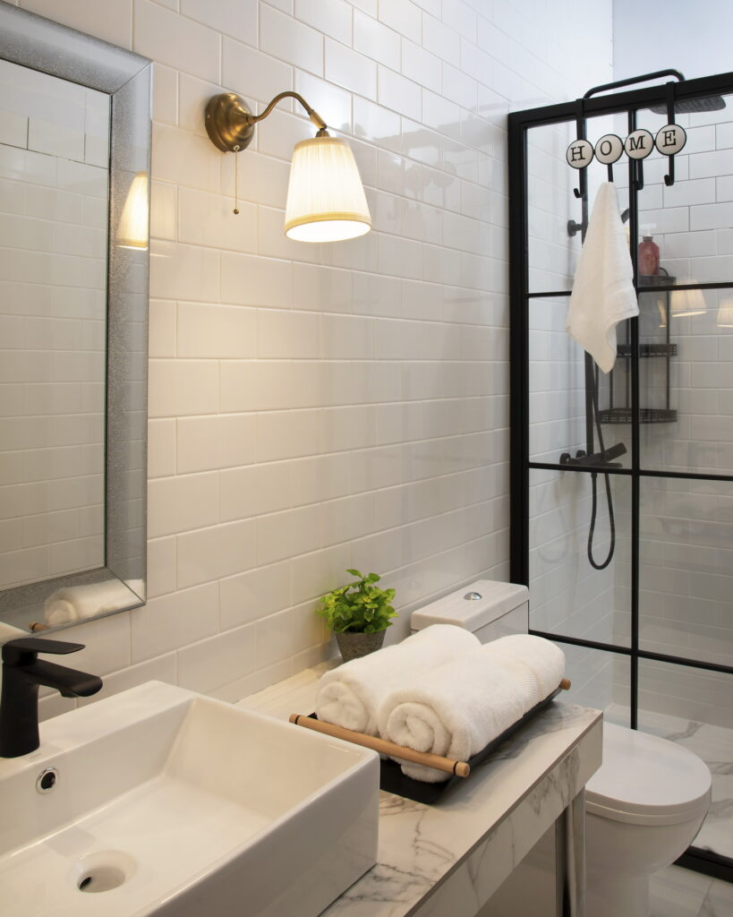 Bathroom with white subway tiles, marble look surfaces, black accents, and modern minimalist interior.