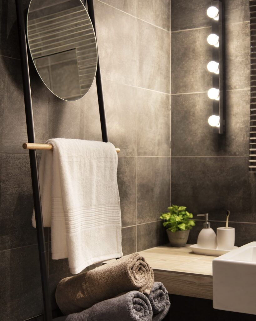 Dark concrete look bathroom with dressing room lights, circular mirror, integrated towel rack.