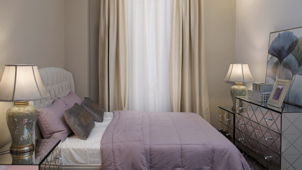 Bedroom in earth tones with blue green painting, dusty pink sheets, and grey, beige, and olive green accents.
