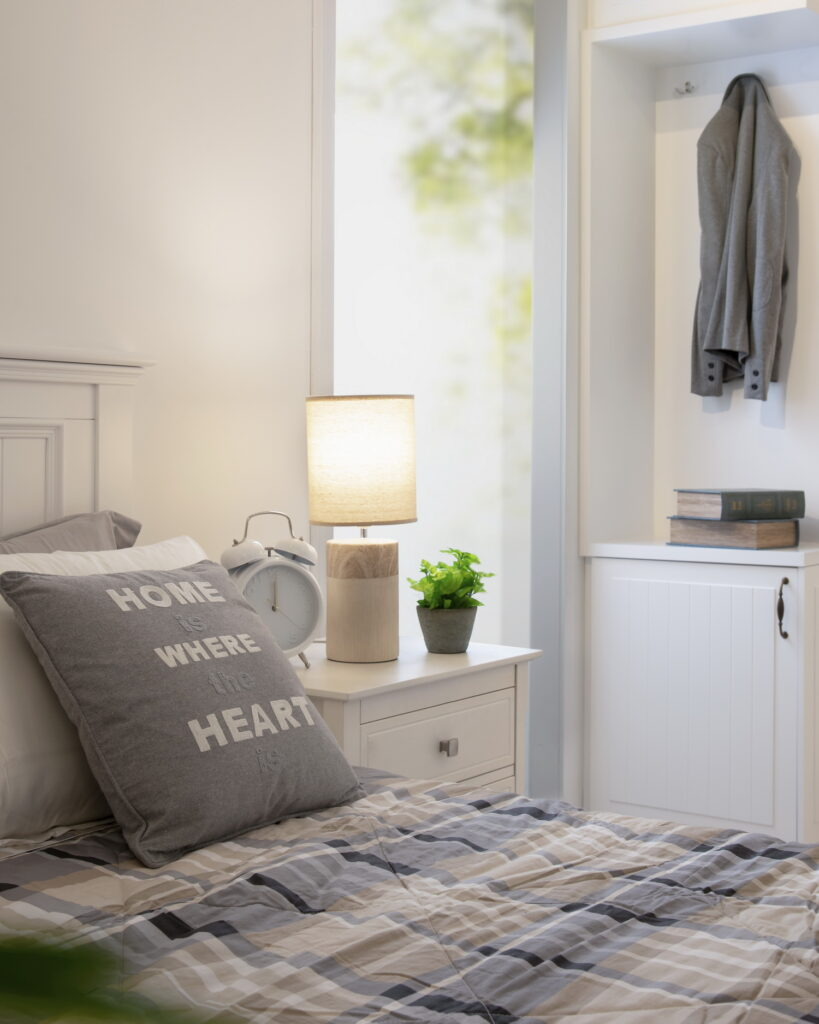 Minimal grey and white bedroom with lots of natural light and tartan bedsheets.