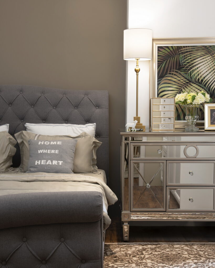 Modern style bed bedroom with tufted grey headboard, neutral bedding.