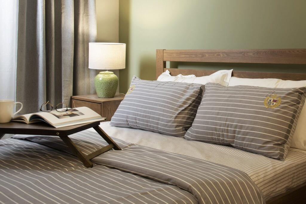 Allergy-safe bedding; grey striped bedding on wooden bedframe.